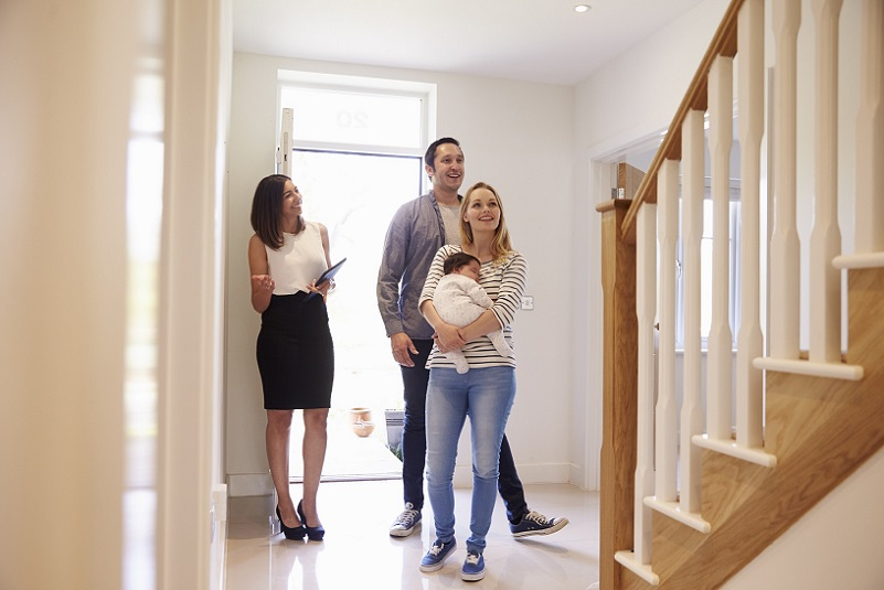 young real estate agent showing a couple a home