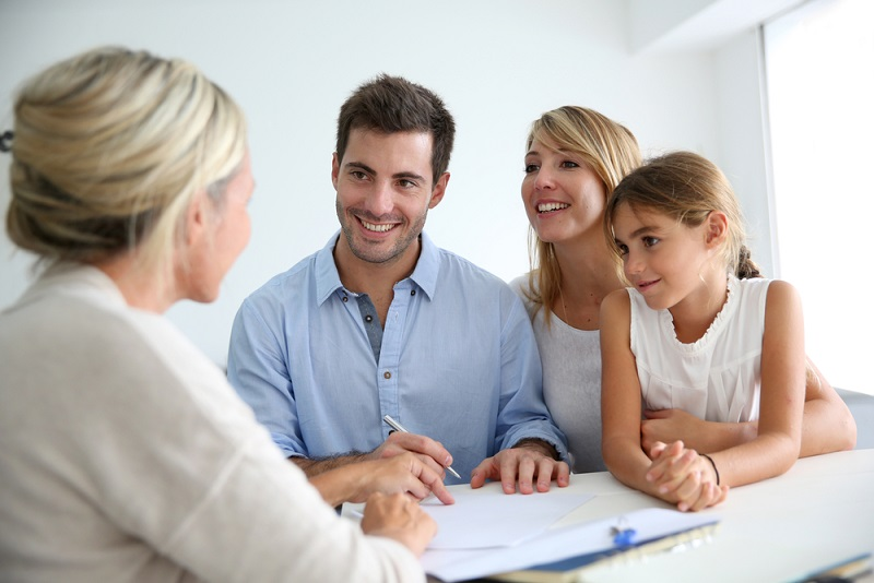A family is talking to blond real estate agent