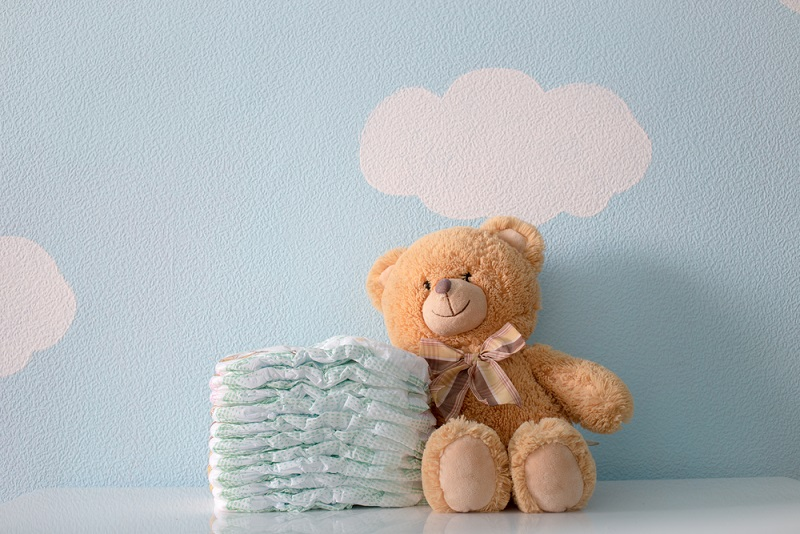 Diapers next to a teddy bear