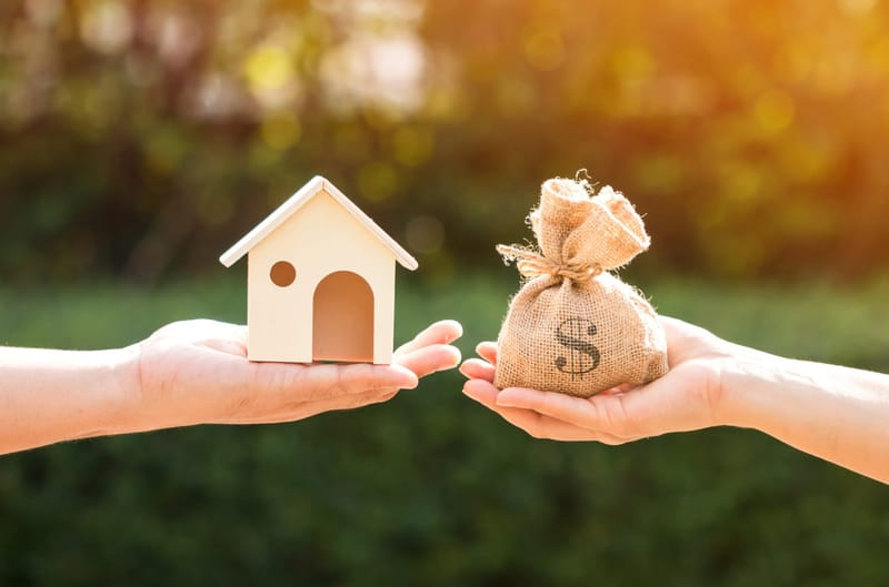 Two hands holding up a small house and a bag of money