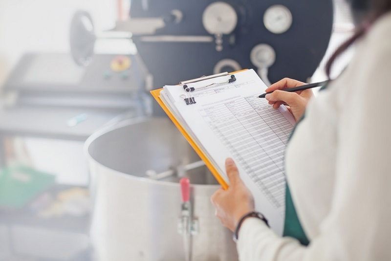 woman standing with checklist in the kitchen