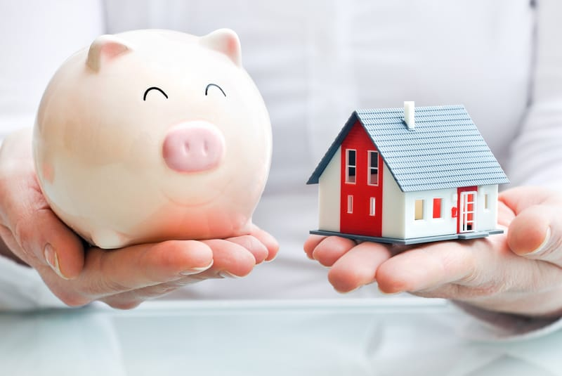 A person holding a piggy bank as well as a house in his hands