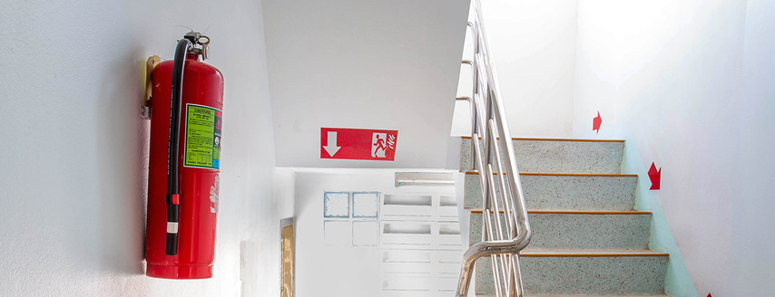 fire extinguisher in a staircase with emergency exit sign seen