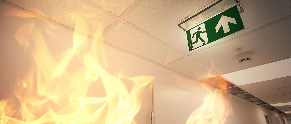fire escape sign being seen next to burning flames