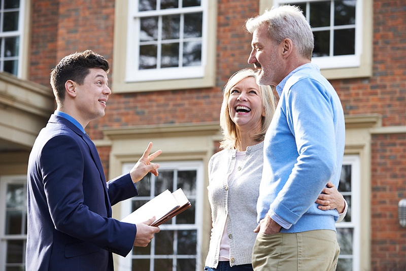 older couple talking to younger real estate agent