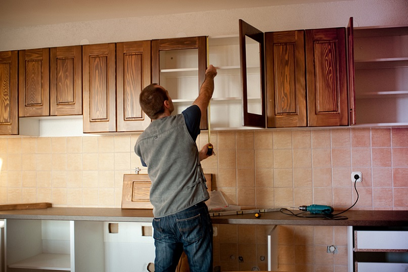 man installing kitchen cabinets