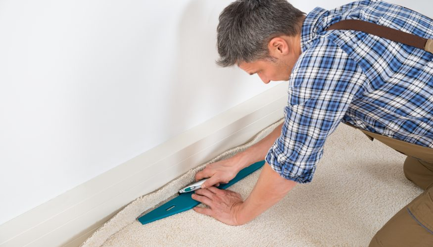 man installing carpet in a home