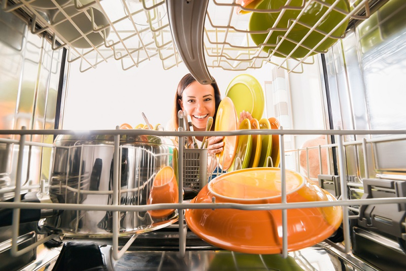 Woman putting dishes into dishwasher