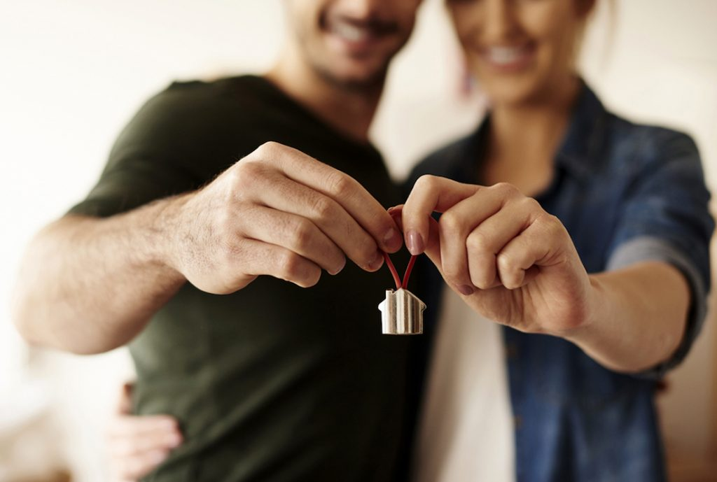 couple holding small version of a home