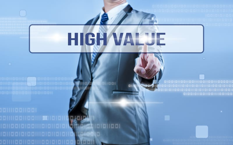 Man in suit pressing a button saying high value