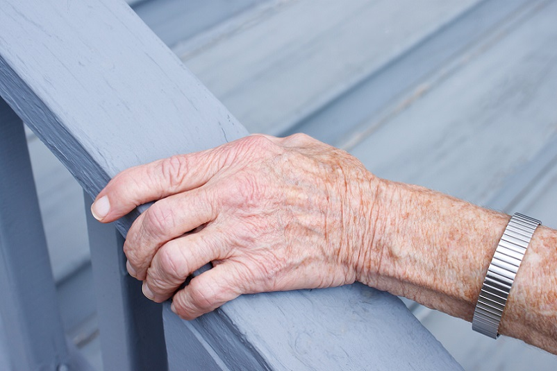 Older person holding handrails