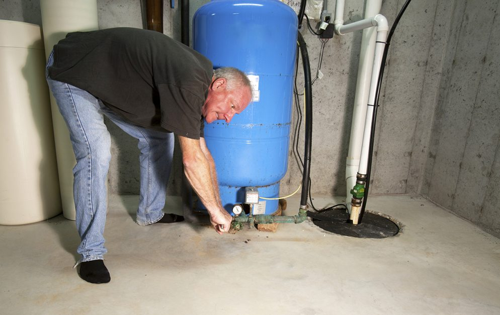 man looking at sump pump in frustration