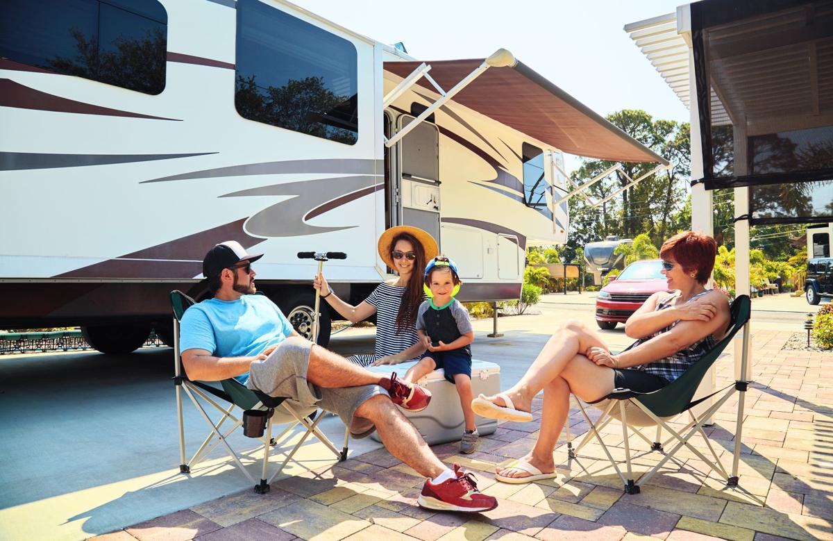 people sitting outside an RV