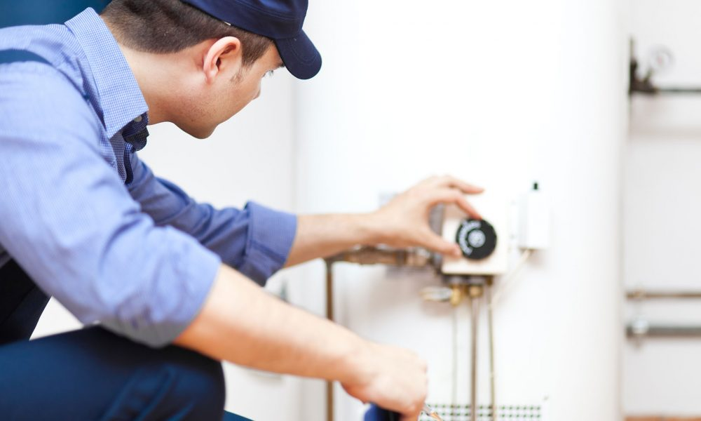 professional adjusting the settings on a water heater